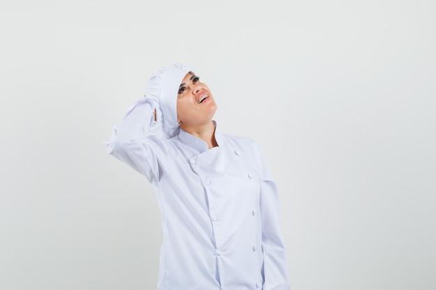 Chef féminin regardant avec la main derrière la tête en uniforme blanc et à la recherche de rêve.