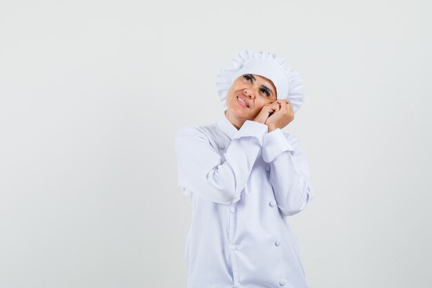Chef féminin s'appuyant sur les paumes comme oreiller en uniforme blanc et à la délicate