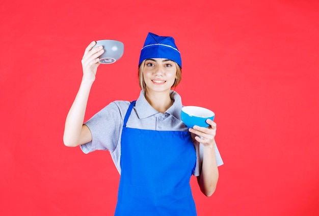 Chef féminin en tablier bleu tenant deux tasses de nouilles en céramique et se confondre au sujet de faire un choix