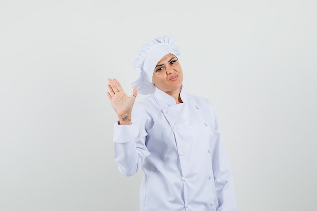 Chef féminin en uniforme blanc, agitant la main pour saluer et à la confiance