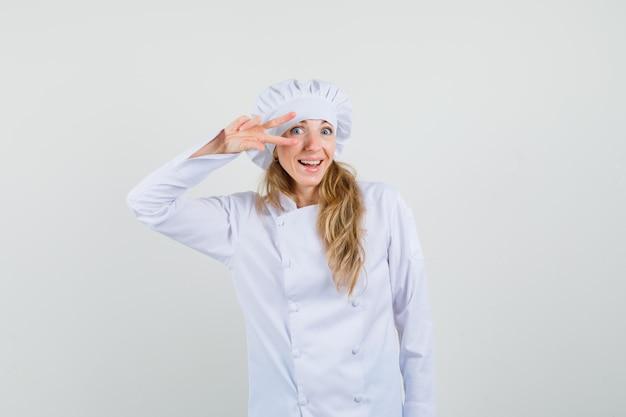 Chef féminin en uniforme blanc montrant v-sign près de l'œil et à la joie