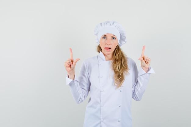 Chef féminin en uniforme blanc pointant vers le haut et qui sort la langue