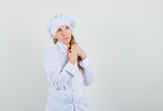 Chef féminin en uniforme blanc à la recherche et à la réflexion