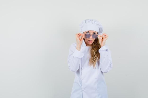 Chef féminin en uniforme blanc regardant la caméra sur des lunettes et à la choqué