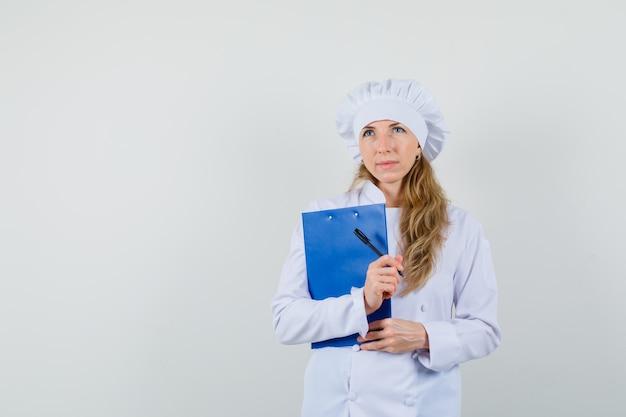 Chef féminin en uniforme blanc tenant le presse-papiers et un stylo et à la réflexion