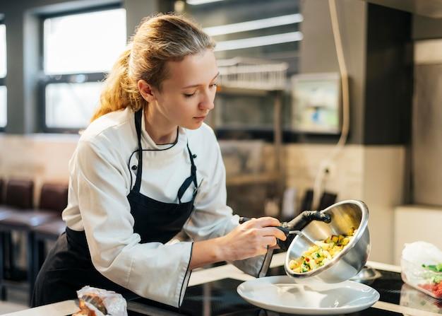 Chef féminin verser de la nourriture sur une assiette