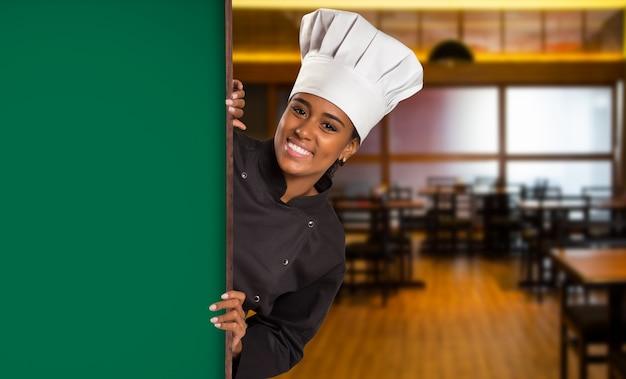 Chef de femme brésilienne noire cuisine regardant la caméra avec panneau vert dans l'espace flou de la maison du vin