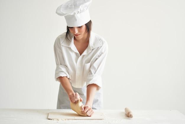 Le chef de femme déroule la pâtisserie de cuisson de boulangerie de pâte