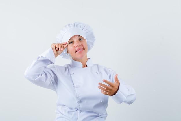 Chef de femme faisant semblant de faire du maquillage en uniforme blanc et à la délicate