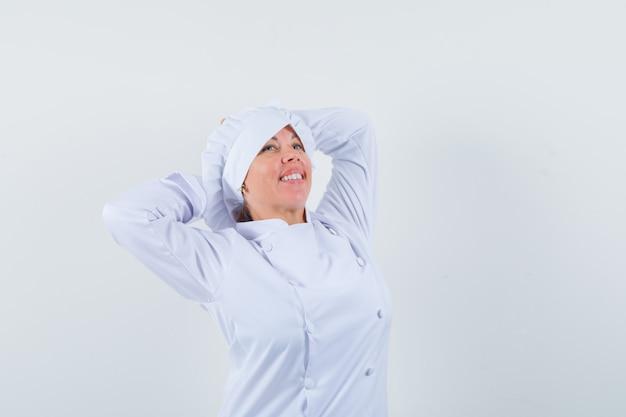 Chef de femme qui s'étend du haut du corps en uniforme blanc et à la détente