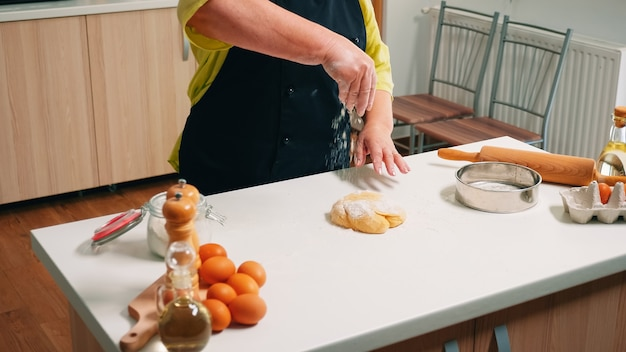 Chef de femme à la retraite cuisine sur table en bois dans la cuisine à domicile. boulanger senior âgé avec bonete et saupoudrage uniforme, tamisant, étalant les ingrédients sur la pâte, cuisant des pizzas et du pain faits maison.