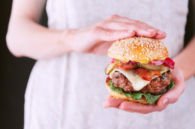 Chef de femme tenant un hamburger fait maison délicieux et juteux cuit dans un style rustique avec une grosse côtelette de boeuf