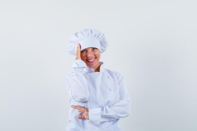 Chef de femme tenant la main sur la tête en uniforme blanc et à la honte
