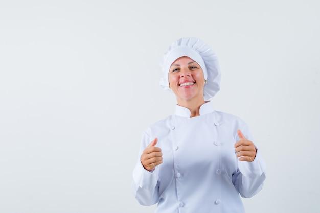 Chef de femme en uniforme blanc montrant le pouce vers le haut et à la joie