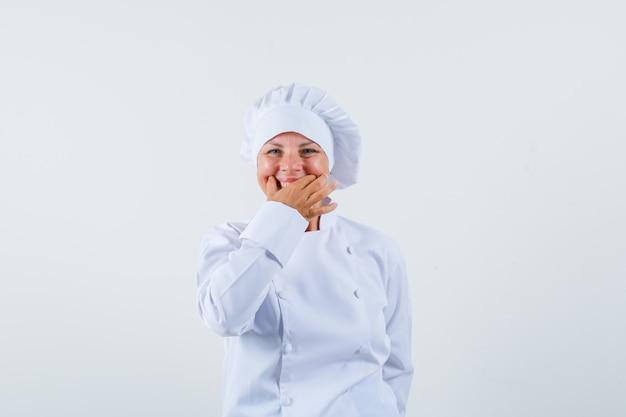 Chef de femme en uniforme blanc tenant la main sur ses dents et à la joyeuse