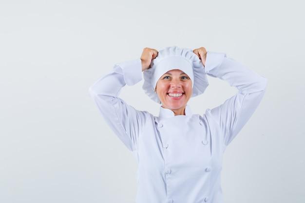 Chef de femme en uniforme blanc tenant les mains sur la tête et à la recherche de plaisir