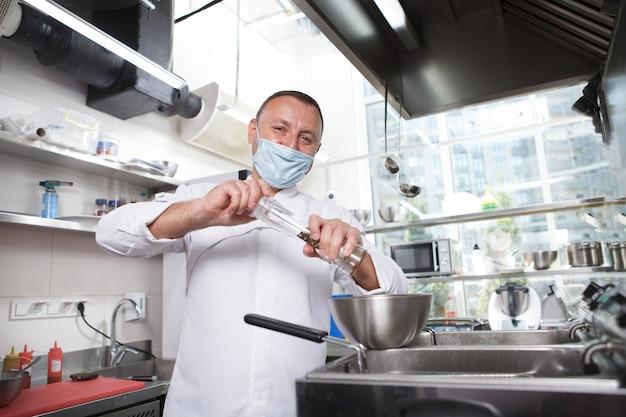 Chef gai portant un masque médical, plat de salage dans un bol dans sa cuisine, espace de copie