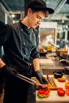 Chef en gants et coupe uniforme morceau de steak juteux