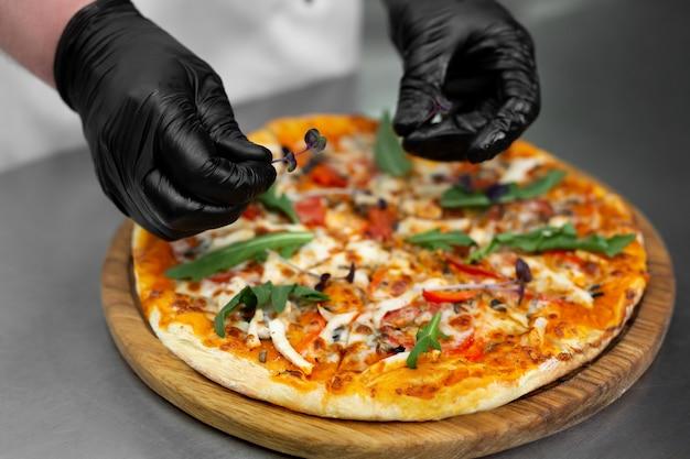 Chef en gants décore la pizza avec des verts