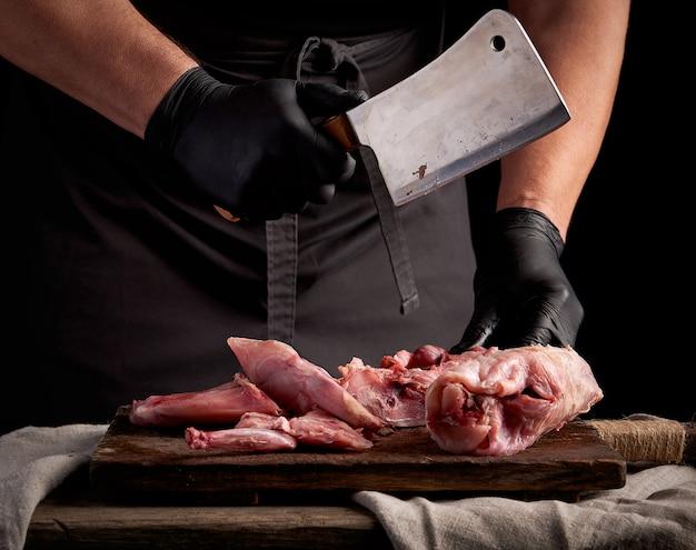 Chef en gants en latex noir est titulaire d'un grand couteau et coupe en morceaux de viande de lapin crue sur une planche à découper en bois brun