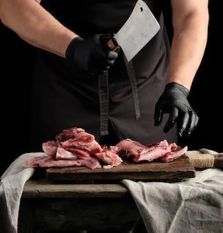 Chef en gants de latex noir tient un grand couteau et coupe en morceaux de viande de lapin crue