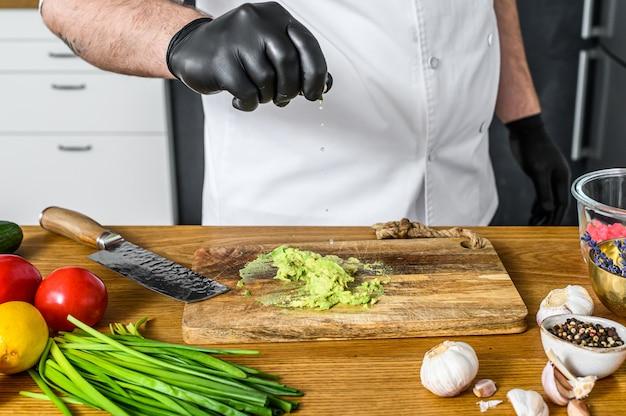 Un chef en gants noirs prépare du guacamole à partir d'avocat frais.