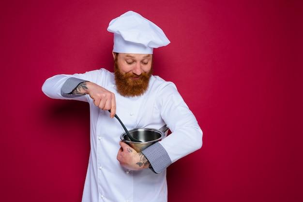 Le chef heureux avec la barbe et le tablier rouge est prêt à cuisiner