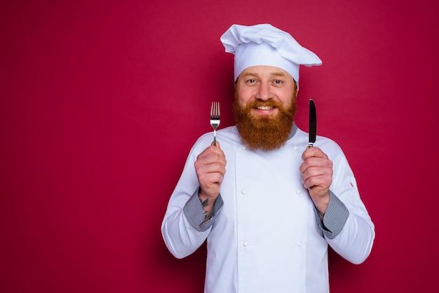 Le chef heureux avec la barbe et le tablier rouge tient des couverts à disposition
