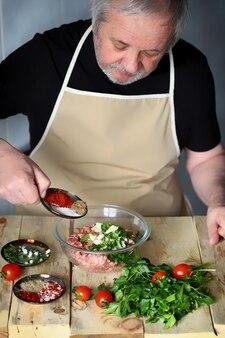 Le chef de l'homme charge les épices dans un bol de viande hachée