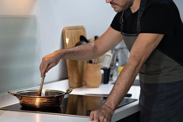 Chef homme cuisine dans la cuisine à la maison