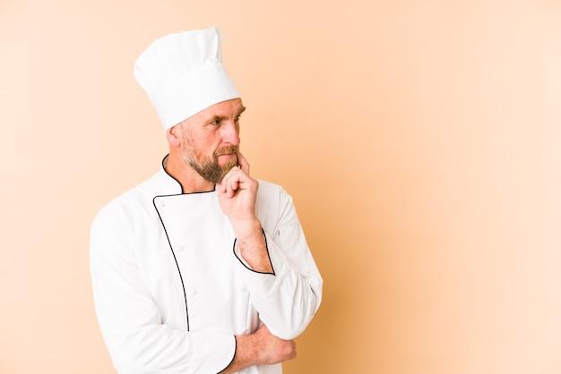 Chef homme isolé sur fond beige détendu penser à quelque chose en regardant un espace de copie.