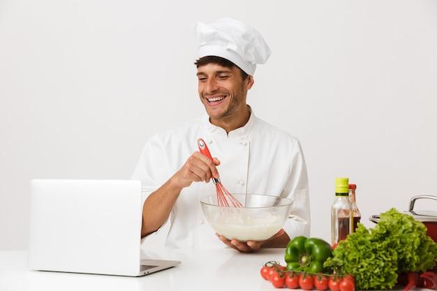 Chef homme isolé sur mur blanc cuisson à l'aide d'un ordinateur portable.