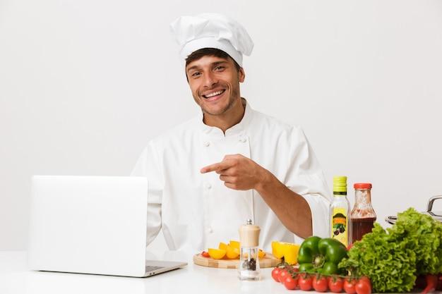 Chef homme isolé sur mur blanc cuisson pointant à l'aide d'un ordinateur portable.