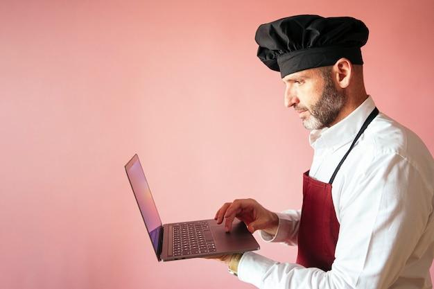 Chef homme avec ordinateur portable avec mur rose