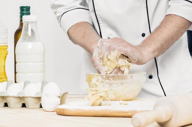 Chef homme en uniforme pétrir la pâte crue dans la cuisine