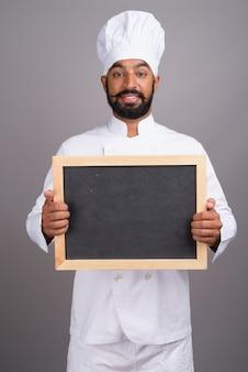 Chef indien tenant un tableau noir vide avec espace copie