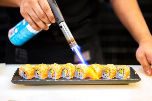 Chef japonais faisant des sushis au restaurant. cuisine japonaise traditionnelle, rouleau de sushi au saumon.