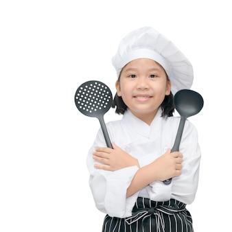 Chef de la jolie asiat tenant des ustensiles de cuisine et sourire isolé sur fond blanc, image carrée.