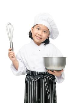 Chef de jolie fille asiatique tenant fouet avec bol et chapeau de cuisinier, tablier isolé sur fond blanc, cuire au four