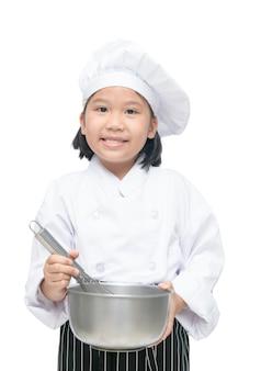 Chef de jolie fille asiatique tenant fouet avec bol et chapeau de cuisinier, tablier isolé sur fond blanc