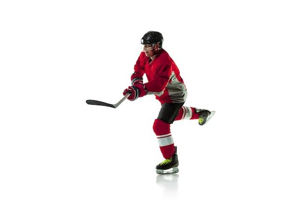 Chef. joueur de hockey masculin avec le bâton sur le court de glace et le fond blanc. sportif portant un équipement et un casque pratiquant. concept de sport, mode de vie sain, mouvement, mouvement, action.