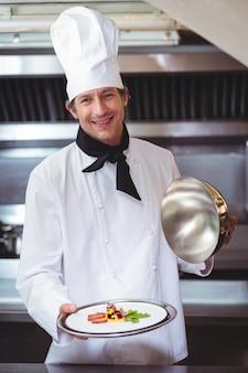 Chef levant une cloche d'un plat
