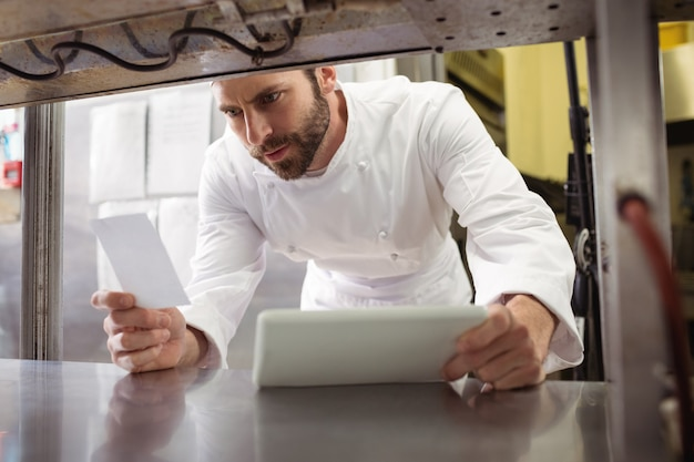 Chef lisant sa commande sur pense-bête dans le comptoir de la cuisine
