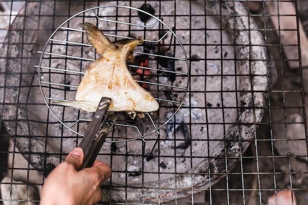 Chef main griller la joue de poisson hamachi kama avec du charbon de bois