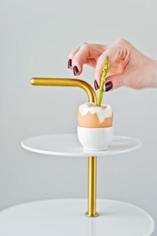 Chef à la main insère un filet d'asperges dans un œuf à la coque