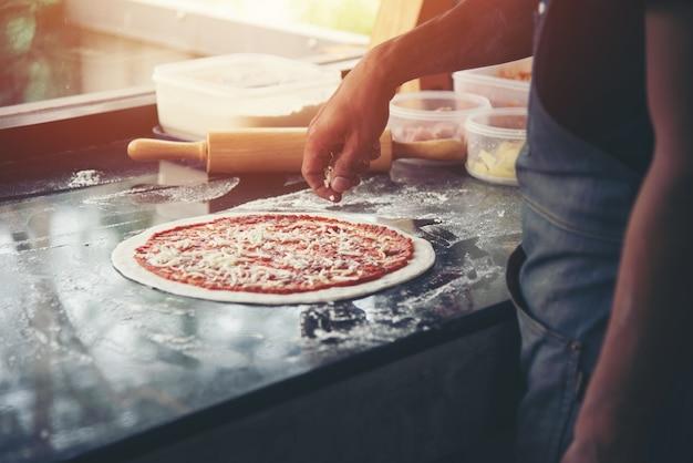 Chef à la main la préparation du fromage à tartiner sur la pizza sur la table en marbre, gros plan faisant de la pizza