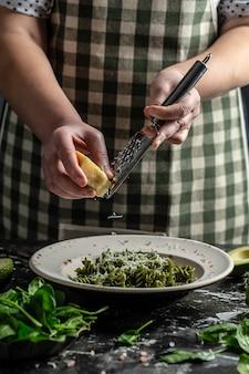 Chef mains la cuisson des pâtes végétaliennes penne avec des feuilles d'épinards frais