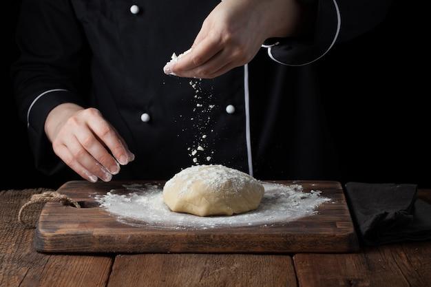 Chef mains verser la farine en poudre sur la pâte crue.