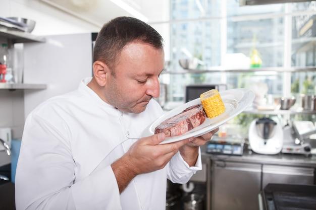 Chef mâle mûr sentant le steak de boeuf marbré dans la cuisine du restaurant