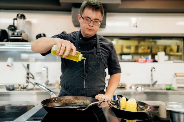 Chef masculin ajoutant de l'huile dans la poêle